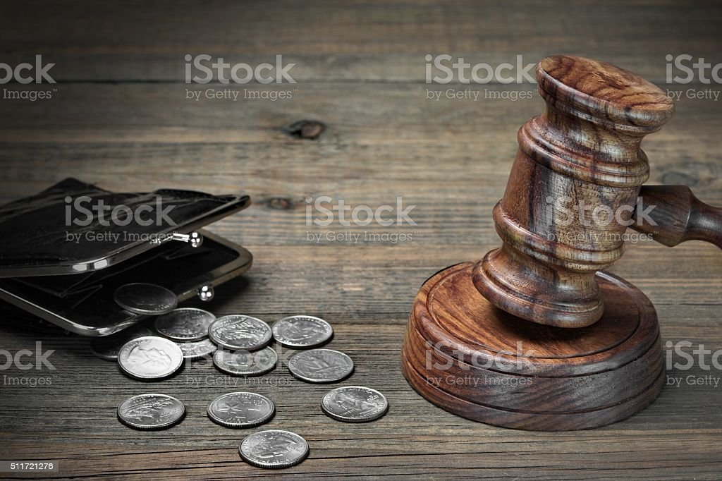 Gavel, Empty Purse, Coins, And Old Book On Wooden Table stock photo