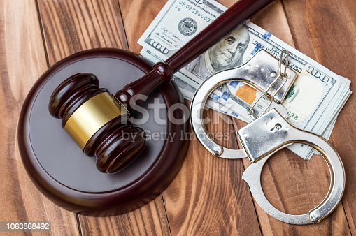 Gavel, handcuffs and money on the table.Top view.