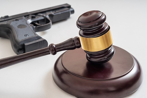 istock Gavel in front of a pistol. Gun laws and legislation concept. 1040303006