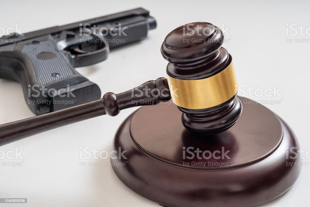 Gavel in front of a pistol. Gun laws and legislation concept. stock photo