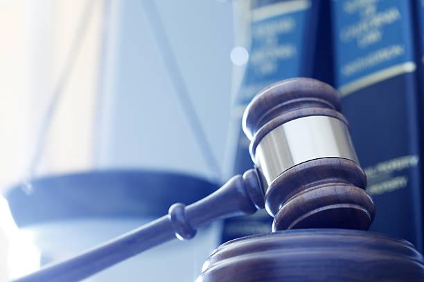 gavel in front of justice scale and law books - waage der gerechtigkeit stock-fotos und bilder
