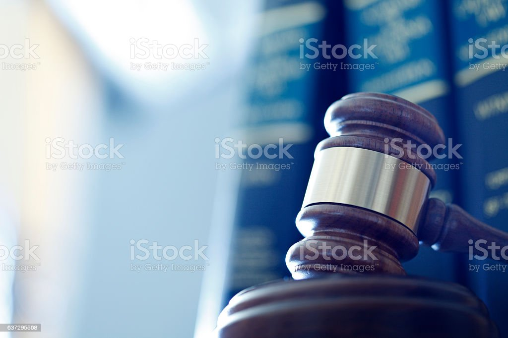 Gavel In Front Of Row Of Law Books A wooden gavel rests on its sounding block in front of a row of law books and an office interior that are out of focus in the background. Photographed using a shallow depth of field. Book Stock Photo