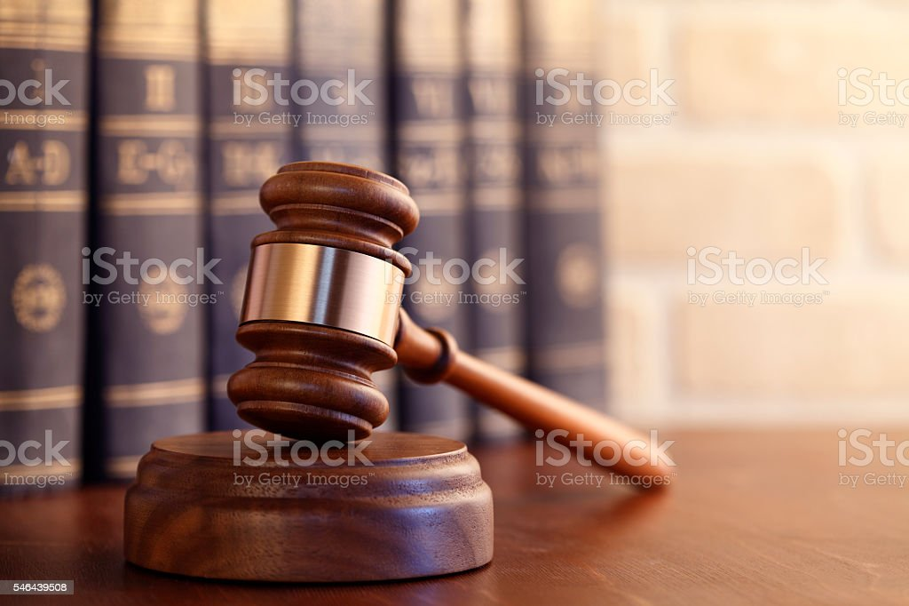 Gavel leaning against a row of law books - foto de acervo