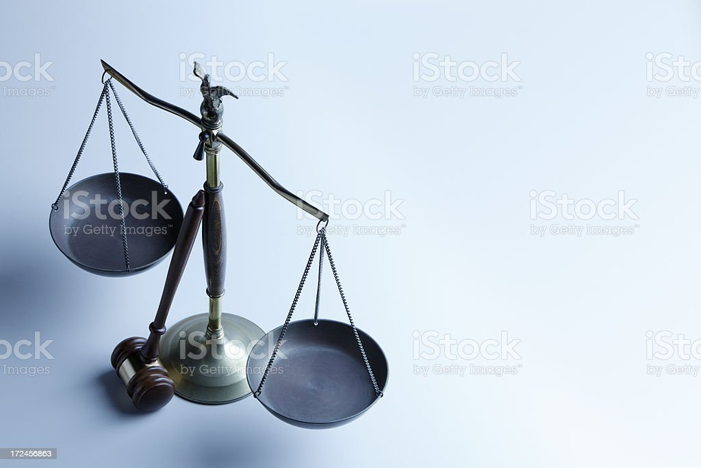 Gavel leaning against scales of justice on blue background stock photo