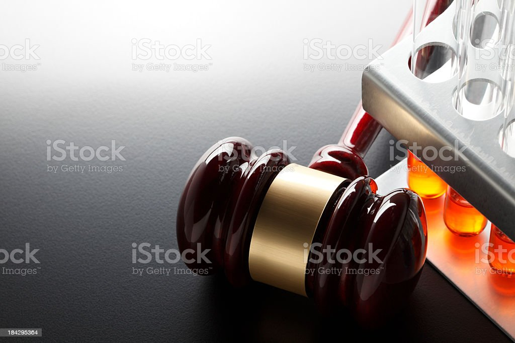 Gavel next to test tube rack on dark gray background royalty-free stock photo