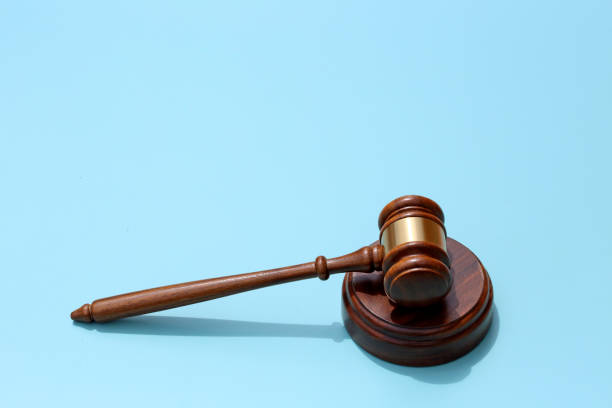 Gavel On A Blue Background A gavel rests on its sound block on a blue background.  The blue background provides ample room for copy and text. lawsuit stock pictures, royalty-free photos & images