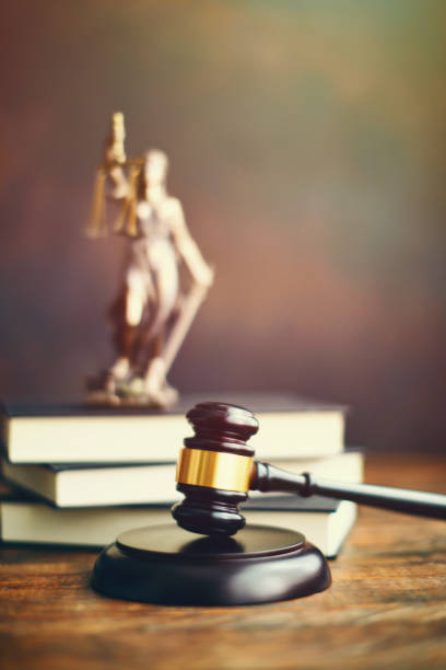 Gavel on desk with Lady Justice stock photo