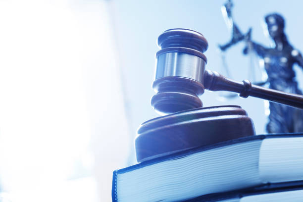 Gavel On Law Book With Lady Justice In The Background stock photo
