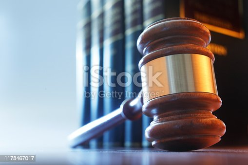 A gavel, photographed from a low camera angle, rests in front of a row of law books.