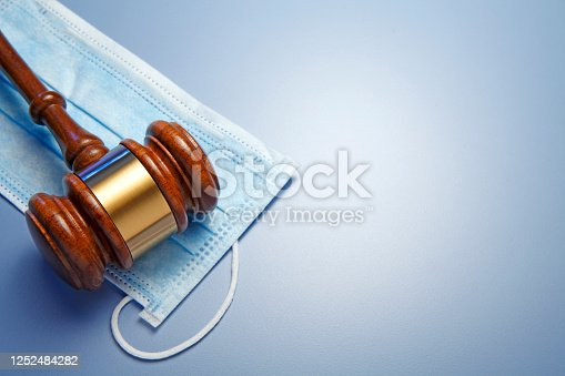 A gavel rests on top of a protective mask on a blue background that provides ample room for copy and text. The image conveys the concept legal issues relating to COVID-19.