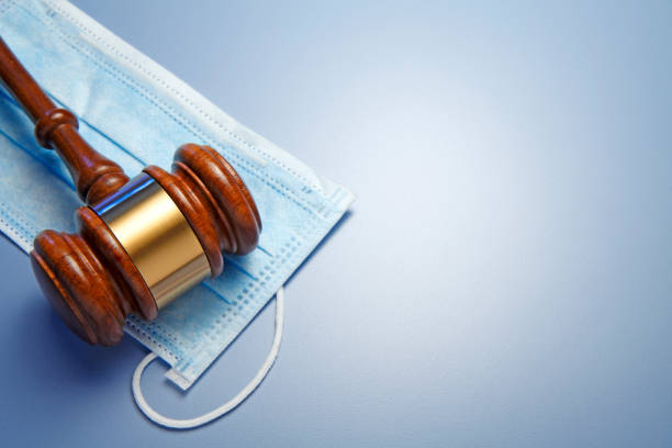 Gavel Resting On A Protective Mask stock photo