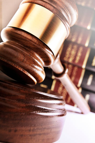 Gavel Resting On Its Sounding Block In Front Of Stack Of Law Books stock photo