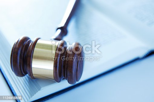 A wooden gavel rests on top of an open law book. The image is photographed using a very shallow depth of field.
