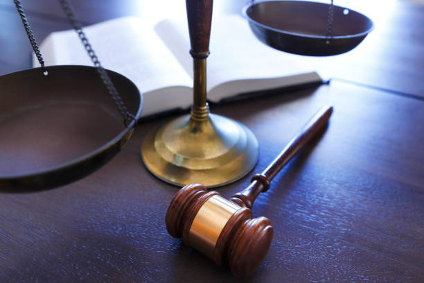 Gavel Rests In Front of Justice Scale And Open Law Book A gavel sits in front of a justice scale and an open law book. lawsuit stock pictures, royalty-free photos & images
