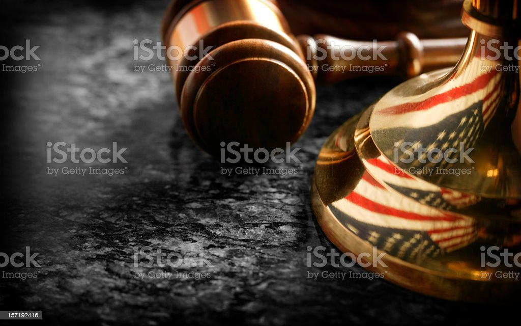 Gavel sitting at base of justice scale with reflection of flag royalty-free stock photo