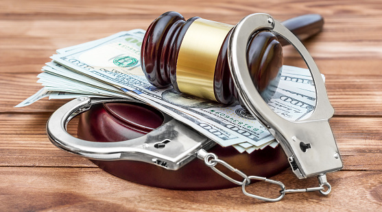 istock Gavel with handcuffs and money on the wooden table. Crime and law concept. 948163962