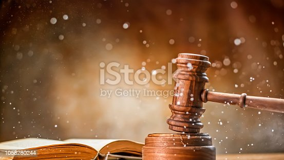 Wooden gavel with open law book and splashing water on table.