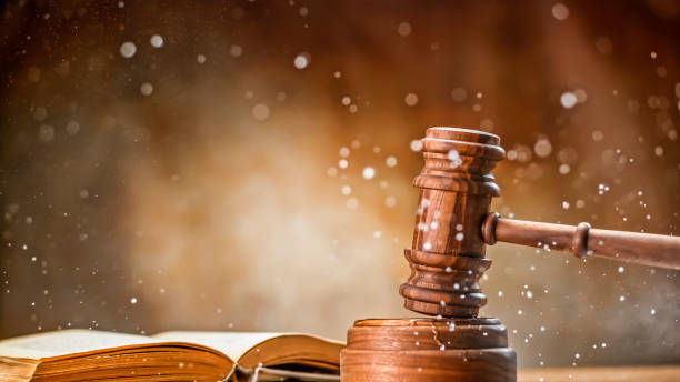 Gavel with law book Wooden gavel with open law book and splashing water on table. legal trial stock pictures, royalty-free photos & images