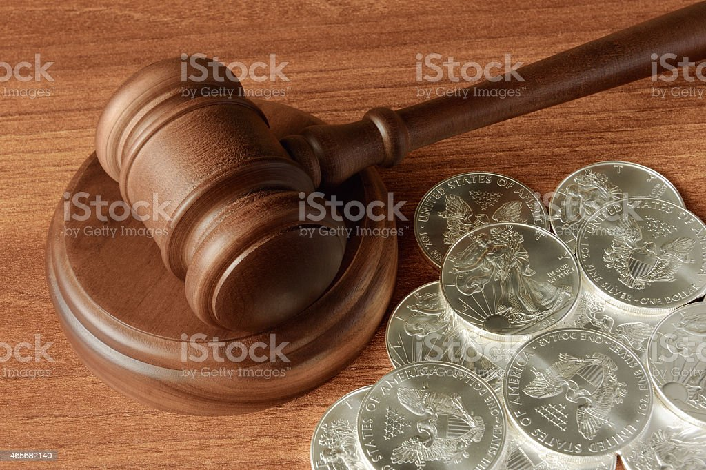 Gavel with silver dollars on wood surface stock photo