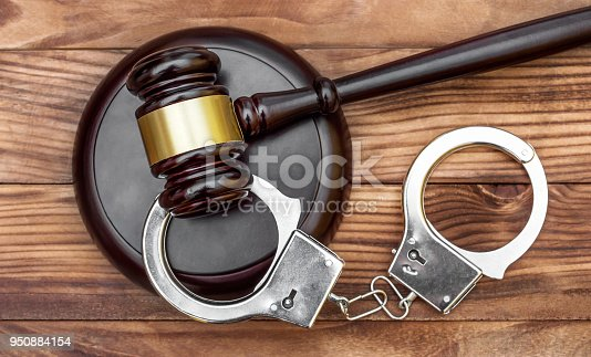 Gavel with stand and handcuffs on the wooden background. Top view.