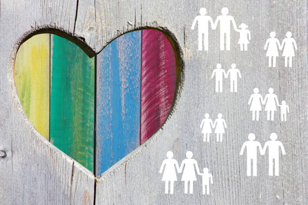Gay and lesbian couples and families on wooden background with multicolor rainbow heart stock photo