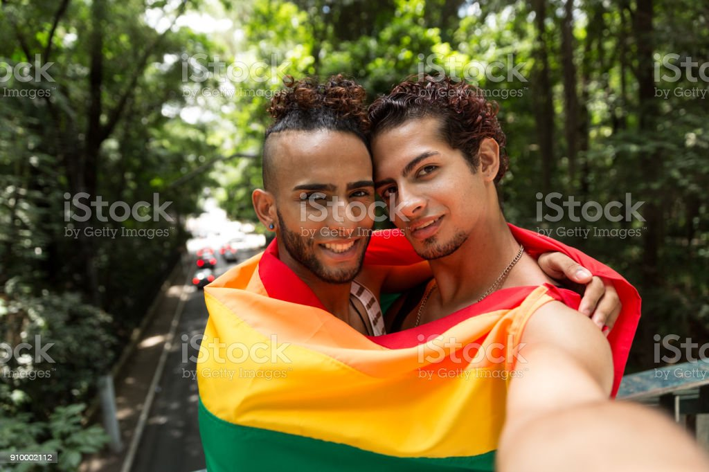 Gay couple at a romantic moment holding the LGBT flag stock photo