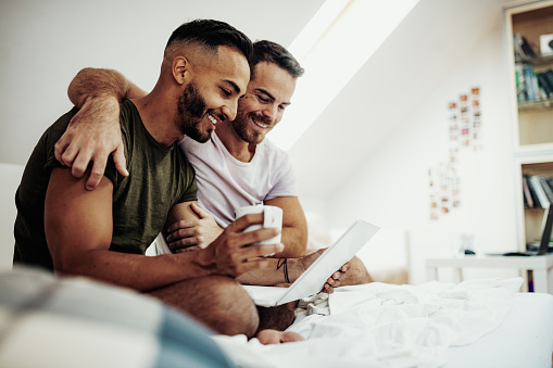 Gay Couple At Home Using Internet And Laptop To Chat With Friends Stock Photo - Download Image Now