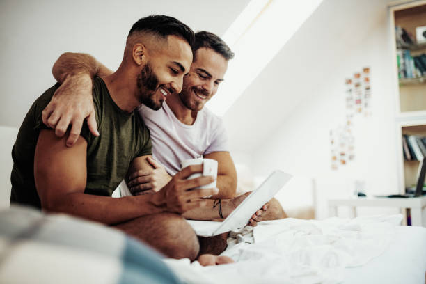 Gay couple at home using internet and laptop to chat with friends Gay couple at home in penthouse gay person stock pictures, royalty-free photos & images