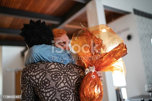 Brazilian family celebrating easter at home, having fun, hugging, talking or standing for portraits. Chocolate easter egg