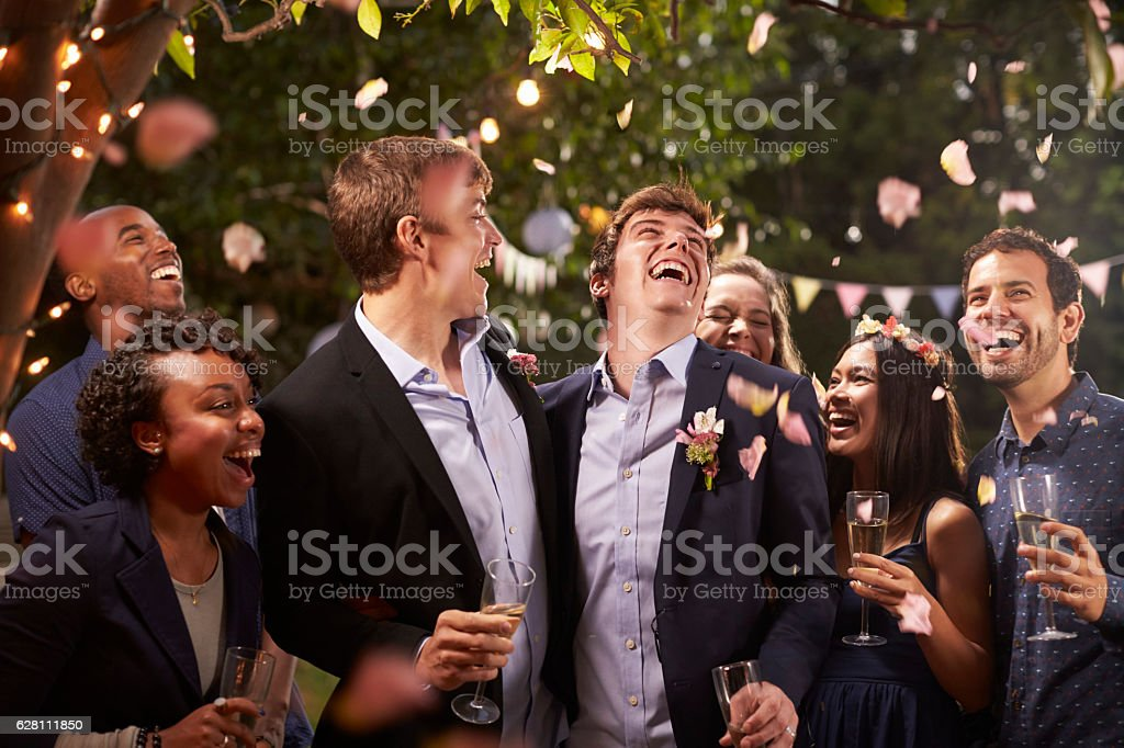 Gay Couple Celebrating Wedding With Party In Backyard stock photo