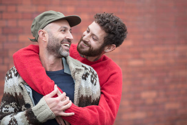 Gay couple cuddling and laughing in front of brick wall Gay couple hanging out gay man stock pictures, royalty-free photos & images