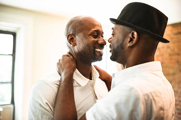 Gay couple dancing together at home stock photo