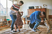 Gay couple dancing with daughter and pug at home. Happy family is enjoying leisure time together. They are at home during weekend.