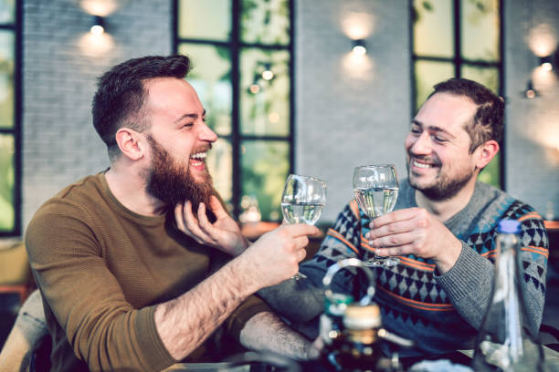 Gay Couple Drinking Water Together And Enjoying Each Other's Company stock photo