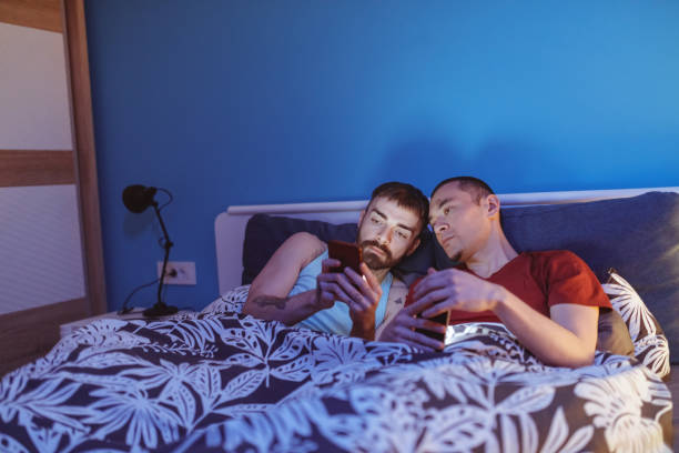 gay couple in bed looking at content on mobile phone - telemóvel ao lado da cama imagens e fotografias de stock