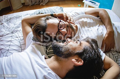 gay men lying in the bed