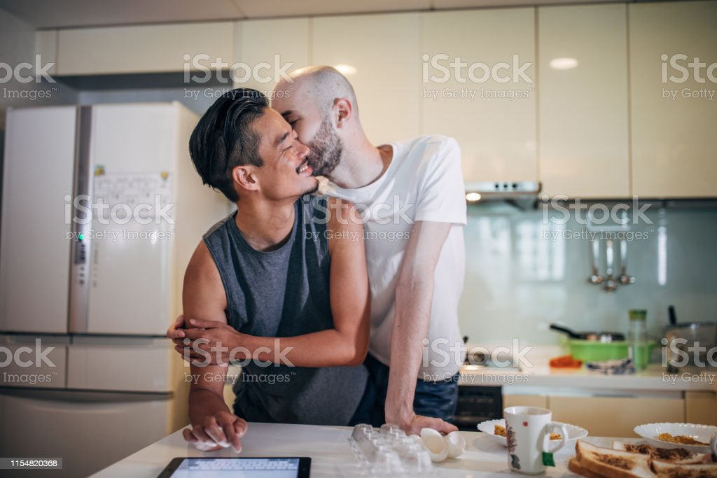 Young multi-ethnic guy couple in the kitchen, making toast...