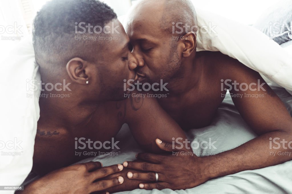 gay couple kissing and make sex in the bed stock photo