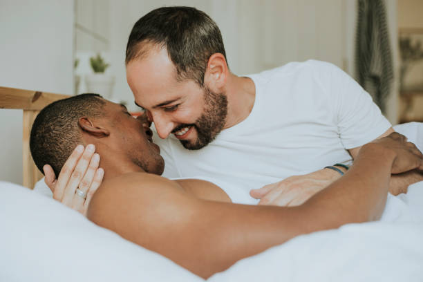 gay couple making out in bed - coppia gay foto e immagini stock