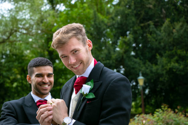 Gay couple of grooms pose for photographs after their wedding ceremony stock photo