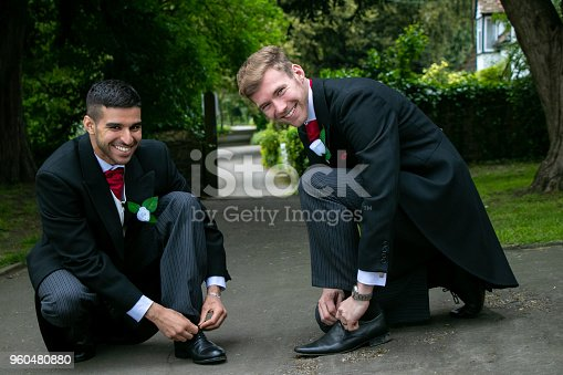 Two gay men or grooms wearing morning suits take time out of posing for photos and and pose for candid shots of them tying their shoe laces.