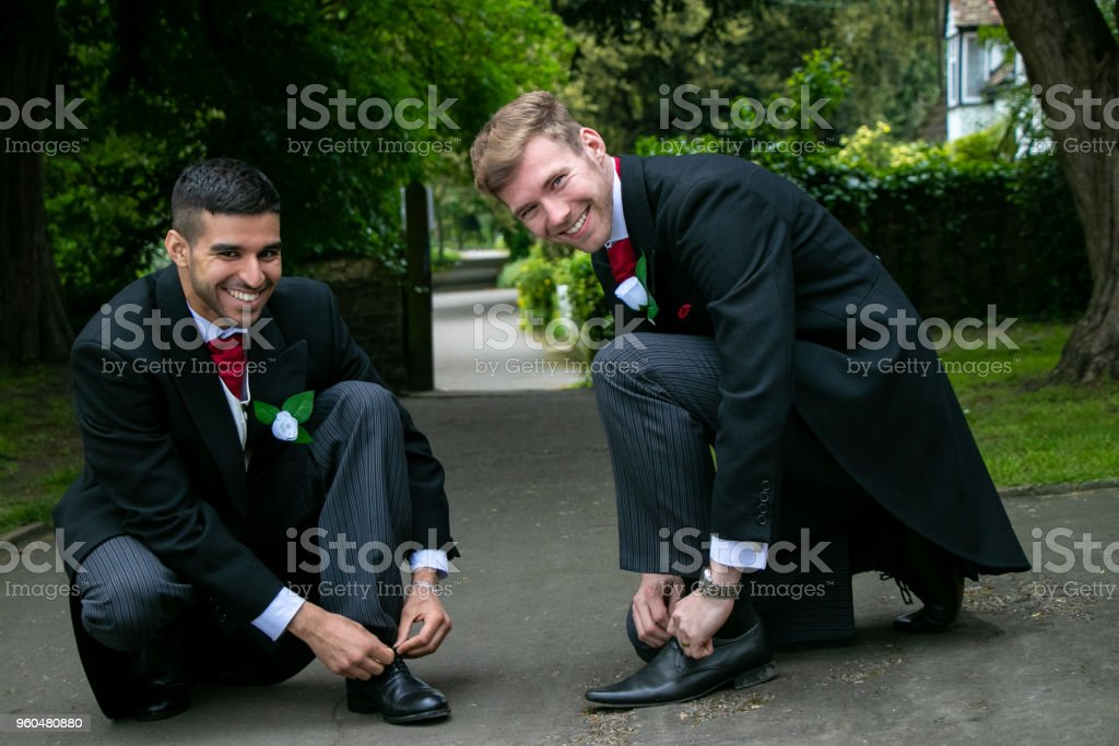 Gay couple of grooms pose for photographs whiel tying shoe laces stock photo