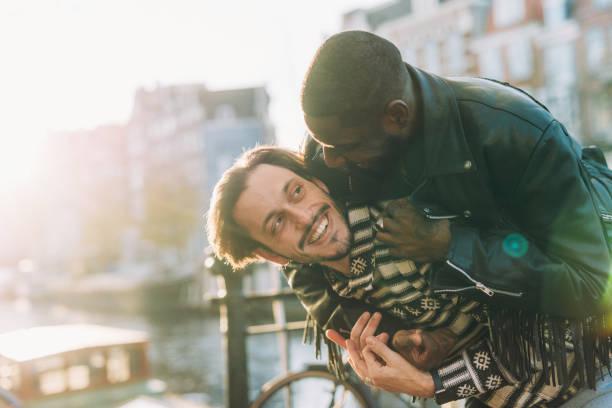 gay paar auf stadt brechen huckepack - paar des gleichen geschlechts im urlaub - hochzeitsreise amsterdam stock-fotos und bilder