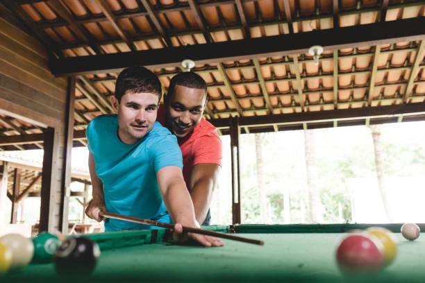 gay paar billard spielen - spieltag vorspeisen stock-fotos und bilder
