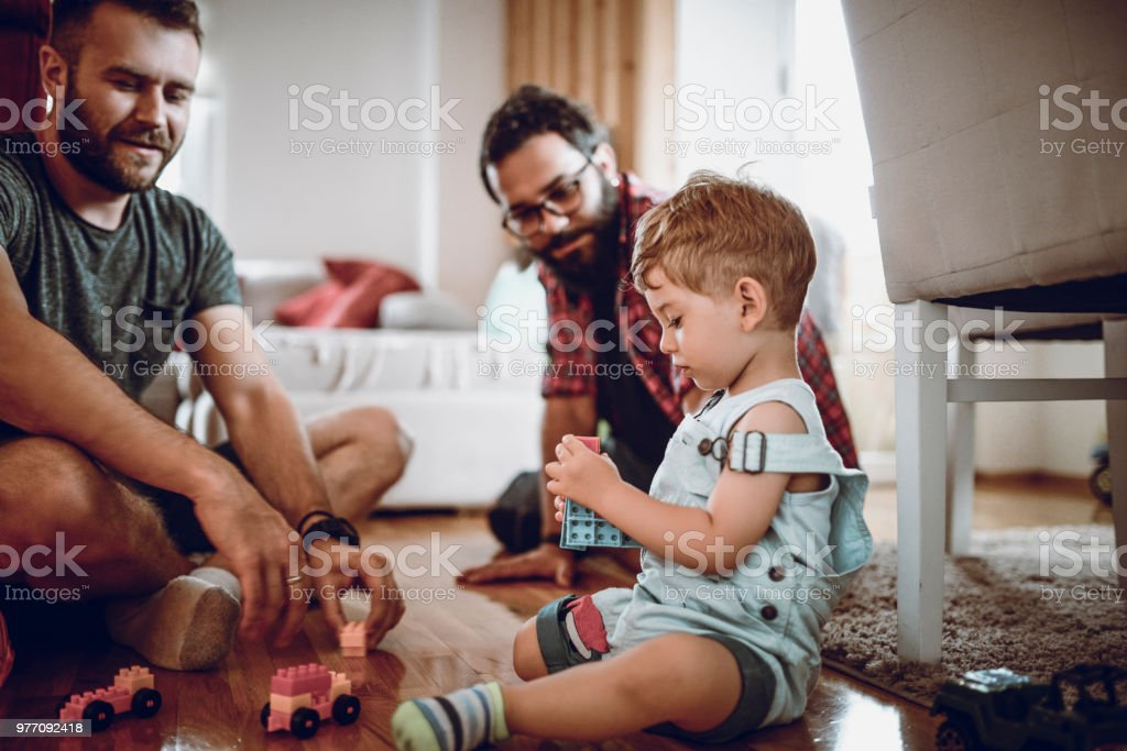 Gay Couple Playing With Adopted Baby Son And His Toys stock photo