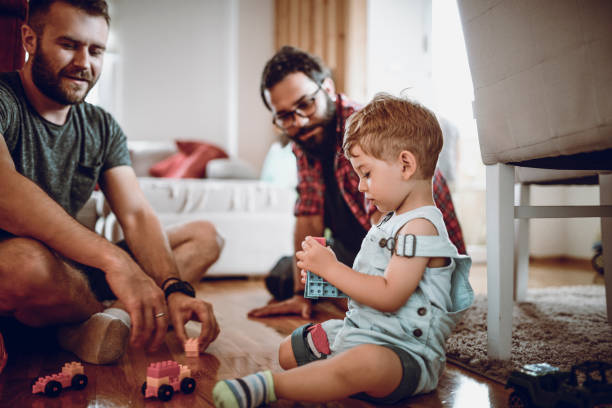 Gay Couple Playing With Adopted Baby Son And His Toys Gay Couple Playing With Adopted Baby Son And His Toys gay person stock pictures, royalty-free photos & images