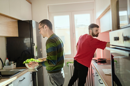 Gay couple preparing breakfast together in the kitchen