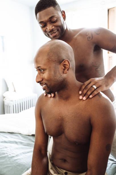 schwules paar teilen die massage im bett - tantra massage stock-fotos und bilder