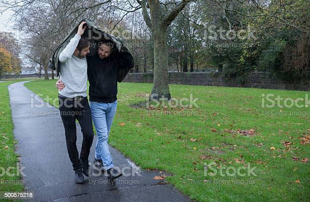 Gay couple sharing a jacket to protect from rain