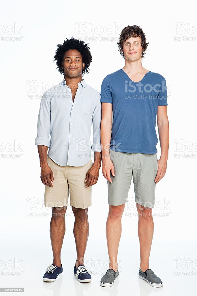 Gay couple standing against white background stock photo